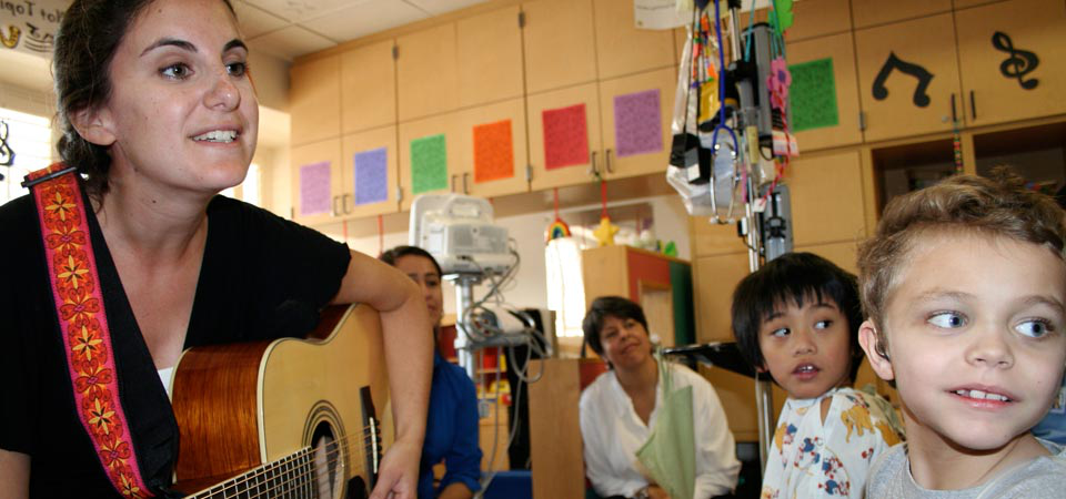 Woman volunteer singing for children at the hospital