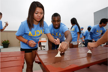 Students painting a wooden table for 志愿者日
