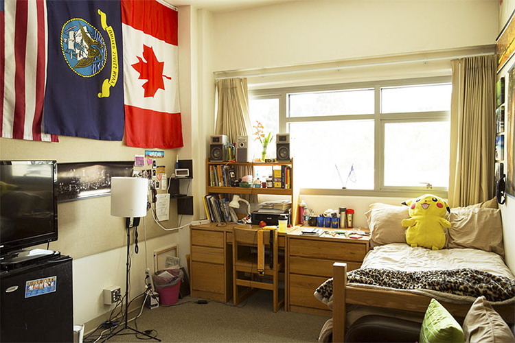 Inside a student residence room with Canadian, Navy, and US flags hanging on wall