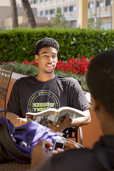 Male student reading a magazine outdoors
