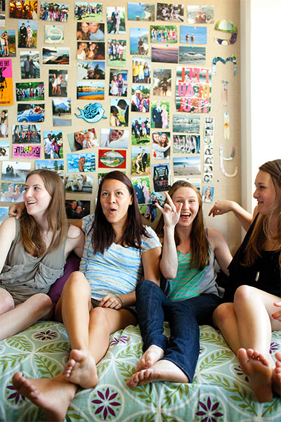 Four female students hanging out in a student residence room with a wall full of photographs behind them
