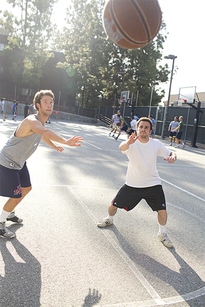 Two male students playing basketball