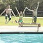 Three students jumping into a swimming pool