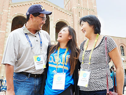 A mother and father smile proudly with their Bruin daughter in front of Royce Hall